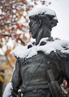 Mountaineer Statute with Snow on its shoulders