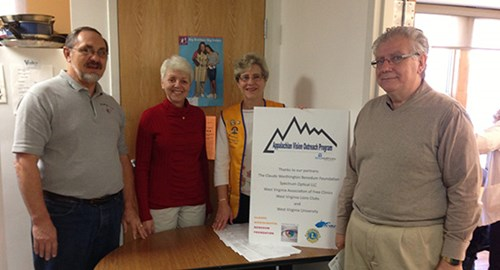 Group photo at a desk with Appalachian Vision Outreach Program screening clinic signage.