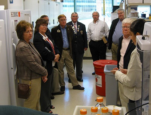 Lions members within a laboratory setting during a tour of the WVU Eye Institute Vision Research Center.