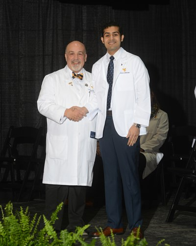 Photo of Ahmed Yousaf receiving his white coat.