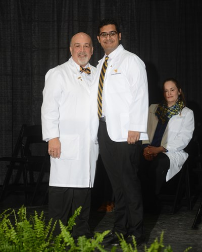 Photo of Muhammad Yousaf receiving his white coat.