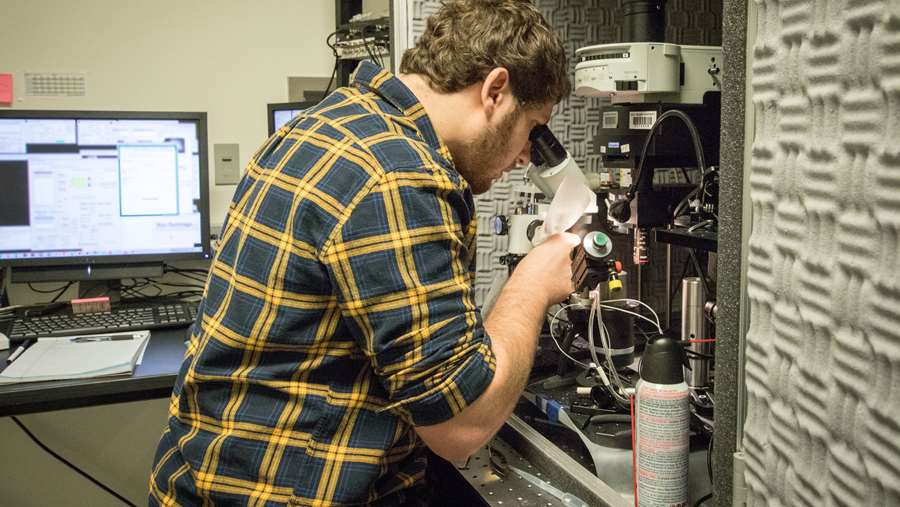 Neuroscience graduate student, Mason McCollum, working with a microscope