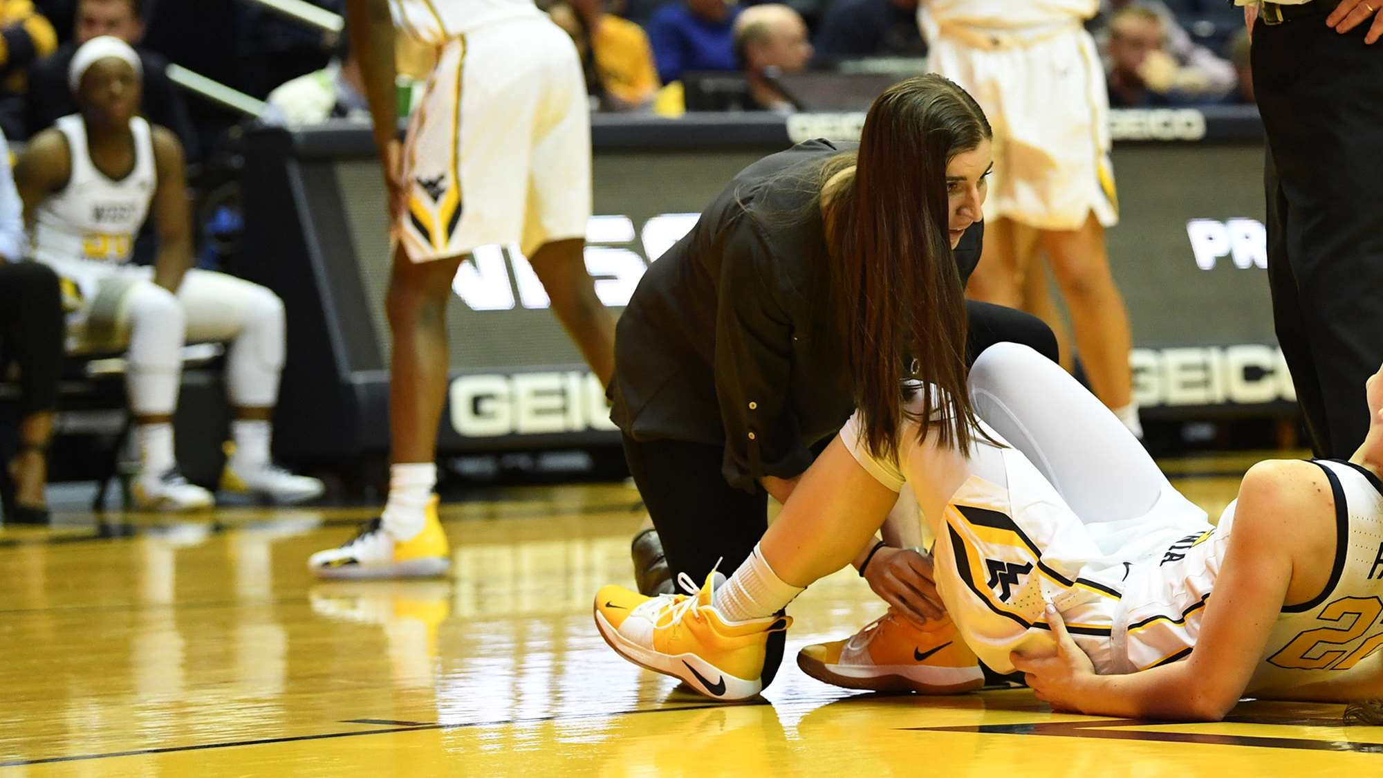 Athletic trainer tends to basketball player on court.