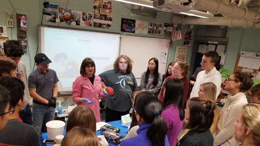 teacher holding a brain model with a group of studnets